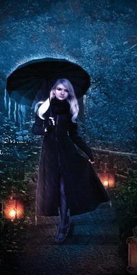 Аватар вконтакте Белокурая девушка в длинном черном пальто с зонтиком в руках, идущая под дождем по тропинке, освещенной яркими фонарями