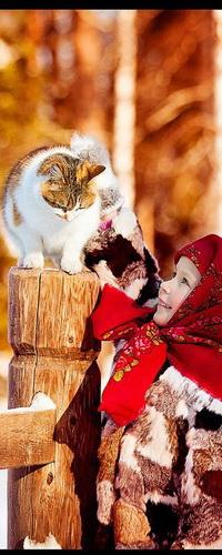 Аватар вконтакте Маленькая, улыбающаяся девочка в красном платке и в шубе, гладит белую, короткошерстную домашнюю кошку, сидящую на деревянном столбике забора, покрытого снегом