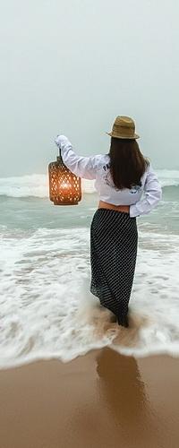 Аватар вконтакте Черноволосая девушка в шляпе на голове, держащая в руке горящей фонарь, стоящая в пенистой, морской воде