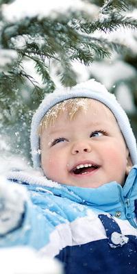 Аватар вконтакте Смеющийся малыш, стоящий под елкой, дергает за ветку и осыпает себя снегом