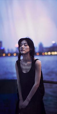 Аватар вконтакте Красивая девушка азиатка стоит закрыв глаза на фоне реки на размытом фоне