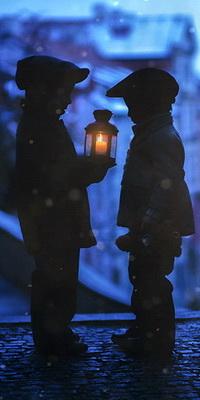 99px.ru аватар Два мальчика, стоящие на брусчатой мостовой на фоне городского вида, у одного из них в руке находится фонарь с горящей внутри свечой