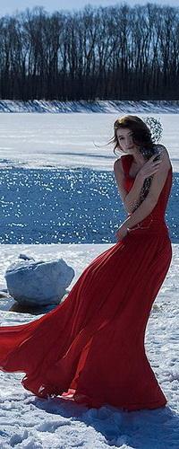 Аватар вконтакте Съежившаяся от холода стройная, черноволосая девушка в длинном красном платье, стоящая на заснеженном берегу незамерзающей реки