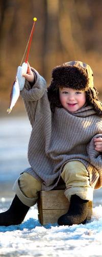 Аватар вконтакте Радостный мальчик, находящийся на зимней рыбалке, держит в руках удочку с пойманной им рыбой