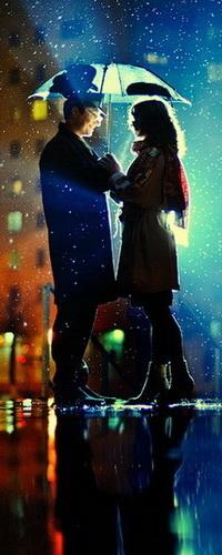 Аватар вконтакте Влюбленная пара, стоящая под зонтом на городской площади на фоне ночного неба и дождя