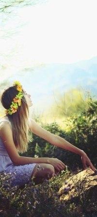 Аватар вконтакте Девушка в венке из цветов сидит в поле, положив руку на камень