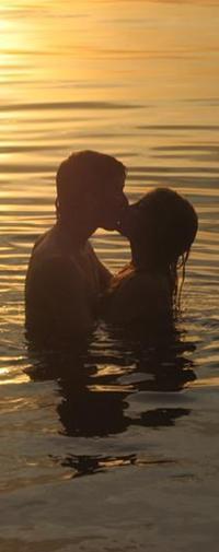 Аватар вконтакте Парень и девушка целуются, стоя обнявшись в море. Солнце на море уходит за горизонт