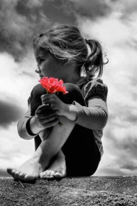 Аватар вконтакте Девочка с красным цветком сидит на земле на фоне облачного неба