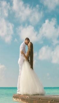 Аватар вконтакте Пара малодоженов целуется, стоя на пирсе на фоне голубого неба с облаками и океана