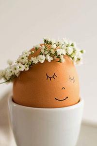 Аватар вконтакте Яйцо в венке из белых цветов с нарисованными закрытыми глазами, носиком и улыбкой