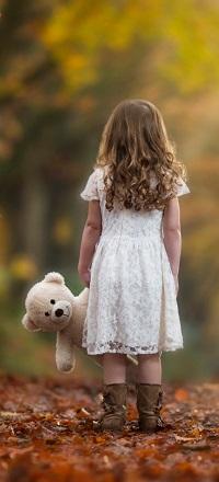 Аватар вконтакте Девочка в белом платье с мишкой в руке стоит спиной на опавших листьях, by Rob Buttle