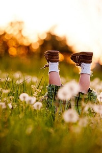 Аватар вконтакте Маленький ребенок лежит в траве с одуванчиками кверху ножками