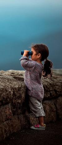 99px.ru аватар Маленькая девочка в вязанном свитере смотрит в бинокль, стоя у каменной ограды