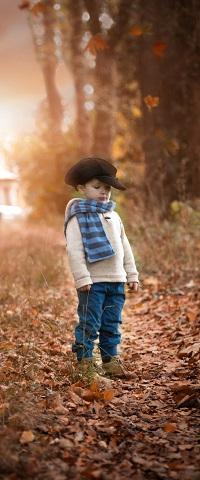 Аватар вконтакте Маленький мальчик в кепке и полосатом шарфе стоит на тропинке усыпанной опавшими листьями