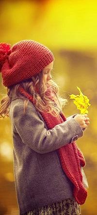 Аватар вконтакте Маленькая девочка в вязанном свитере и шапке держит в руках кленовый лист