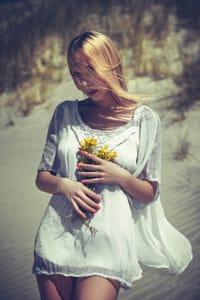 Аватар вконтакте Девушка в белом платье с желтыми цветами в руках стоит на фоне водоема, фотограф Ruslan Bolgov