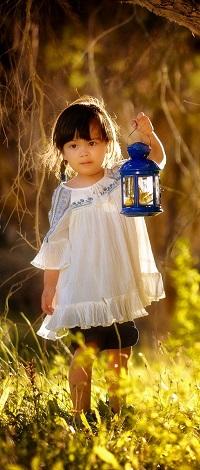 Аватар вконтакте Маленькая девочка азиатка держит в руке синий фонарь, стоя в траве