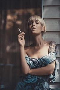 Аватар вконтакте Девушка с сигаретой стоит у стены дома