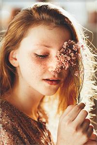 Аватар вконтакте Рыжая девушка с веснушками приложила полевые цветы к глазу