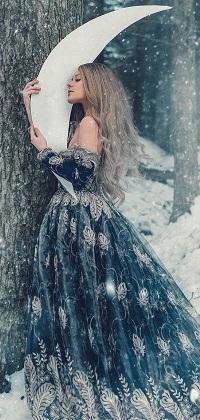 Аватар вконтакте Блондинка в синем платье с вышивкой держит в руках месяц, стоя у дерева в зимнем лесу