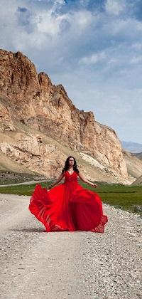 Аватар вконтакте Брюнетка в красном платье стоит на каменистой дороге на фоне гор