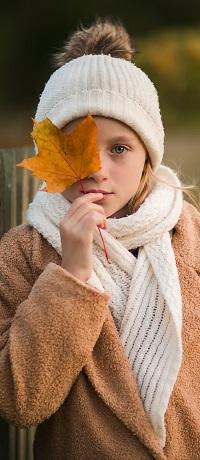 Аватар вконтакте Девочка в вязаной шапочке и шарфе прикрыла листиком клена один глаз