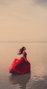 Аватар вконтакте Девушка в красном развевающемся платье стоит воде на берегу моря в профиль