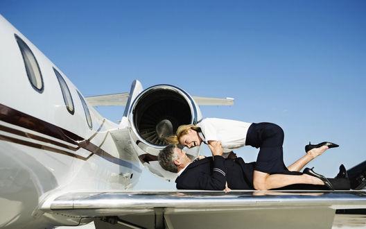 Обои Любовь стюардессы с пилотом на крыле самолета