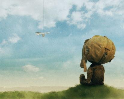 Обои Игрушечный медвежонок мечтательно смотрит в небо, где пролетает самолётик на верёвочке