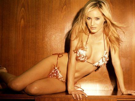 Обои Блондинка в эксклюзивном купальнике соблазнительно поглядывает на фотографа
