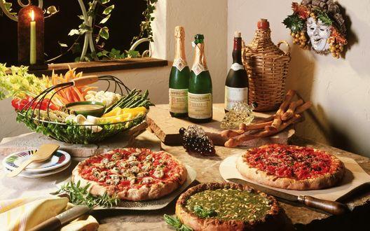 Обои Итальянская кухня. Пышно накрыт стол-пиццы с разными начинками, овощи, красиво нарезанные, там можно различить спаржу, виднеются ещё грибы, посредине этого блюда соус, стол также украшают и изысканные вина, горит свеча и над столом висит маска Бахуса