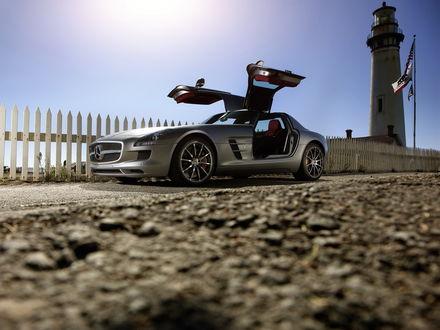 Обои Серебристый автомобиль Mercedes-Benz AMG SLS 63 / Мерседес-Бенс АМГ СЛС 63 стоит возле маяка
