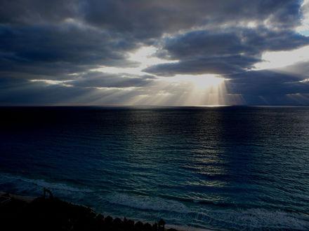 Обои Черно-синий океан, лучи солнца пробиваются сквозь облака