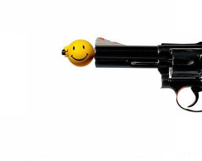 Обои Револьвер стреляет смайлами