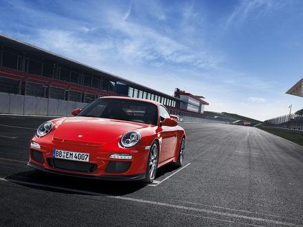Обои Новенькая красная машина на гоночной трассе
