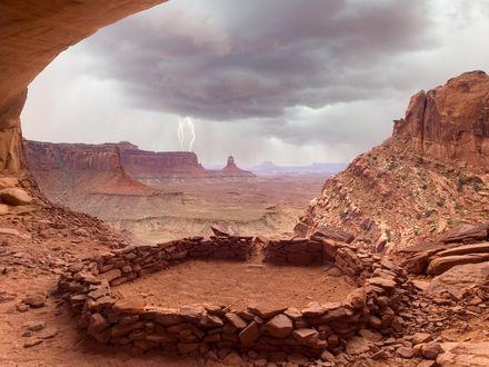 Обои Каньон с кучей мелких камней, вдалеке молния и тучи