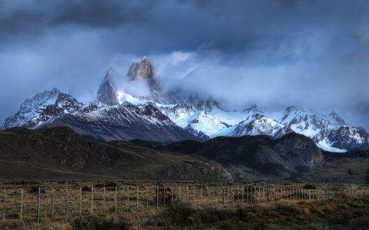 Обои Туманные горы вдали окутанны облаками
