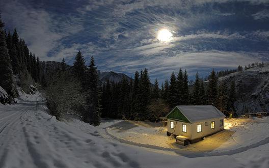 Обои В глубине леса утопает в снегу дом с ярко освещёнными окнами, над ним сквозь облака пробивается свет полной луны