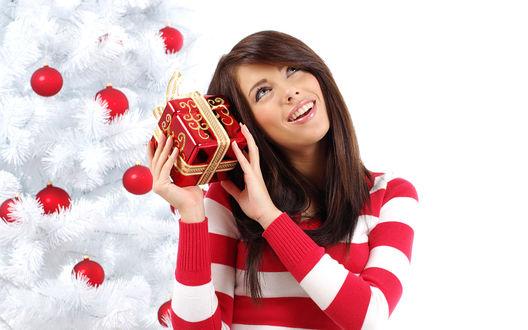 Обои Девушка с мечтательным видом пытается угадать что внутри подарка