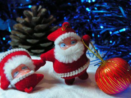 Обои Два игрушечных Деда Мороза рядом с ёлочкой