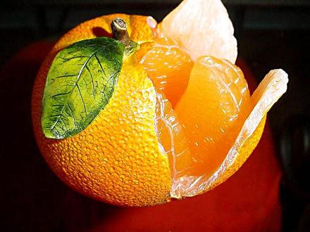 Обои Муляж в виде полу-очищенного сочного апельсин на темном фоне