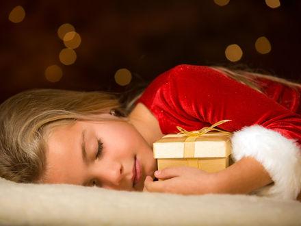 Обои Милая девочка уснула с подарком