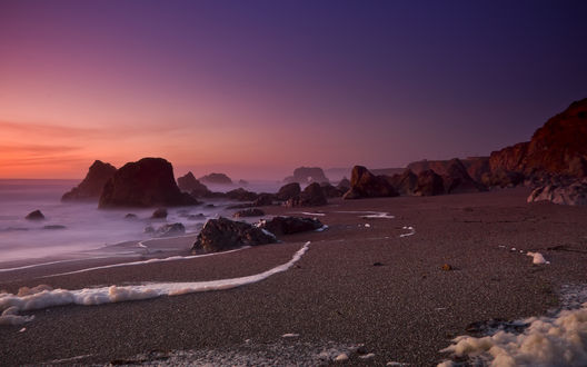 Обои Утренняя дымка над морем и каменистый берег