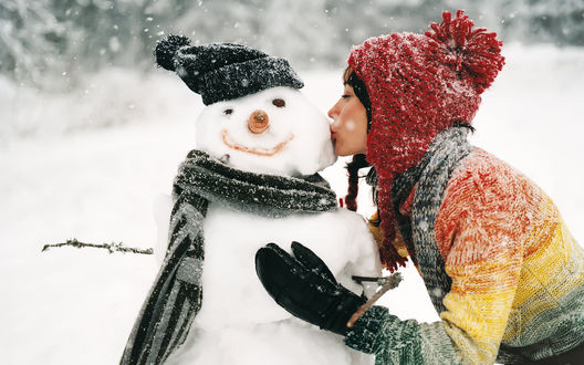 Обои Девушка нежно целует снеговика в холодную щёку