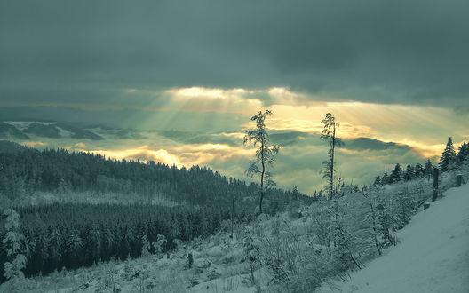 Обои Заснеженные склоны и лучи солнца прорывающиеся сквозь тучи