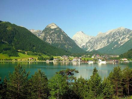 Обои Вид на город, расположенный между снежными вершинами и озером