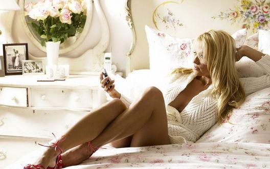 Обои Девушка на кровати с телефоном и букет роз на тумбочке