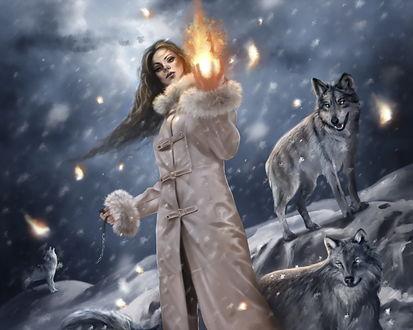 Обои Магия огня. Девушка стоит посреди стаи волков, которые завороженно смотрят на светящийся в её руках огненный шар.