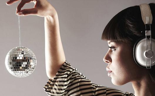 Обои Девушка в наушниках смотрит на ёлочную игрушку, воображая что это дискотечный зеркальный шар