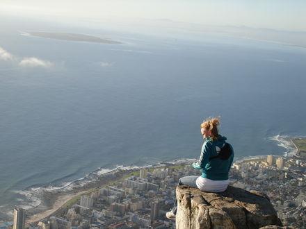 Обои Девушка сидит на скале над городом на побережье
